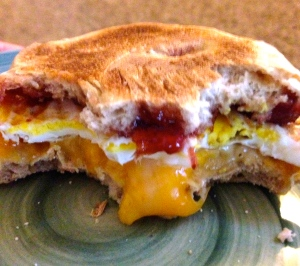 English muffin with strawberry jelly, 1 fried egg and a cheese slice